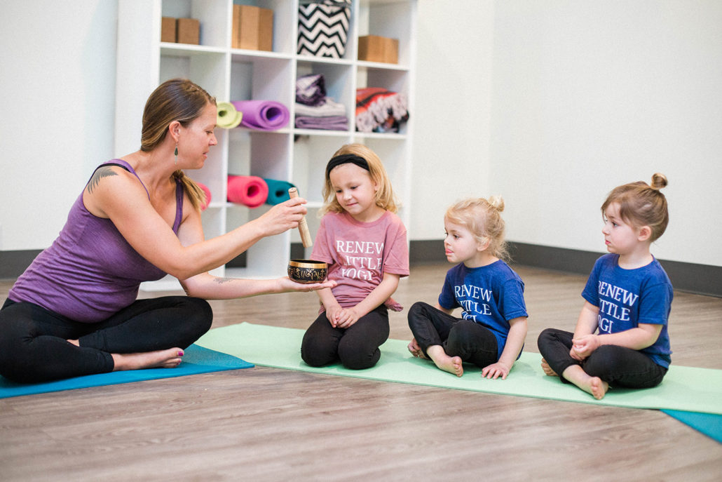 teacher handing singing bowl to kids in a yoga class