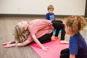Two kids practicing a partner yoga pose while two other kids watch