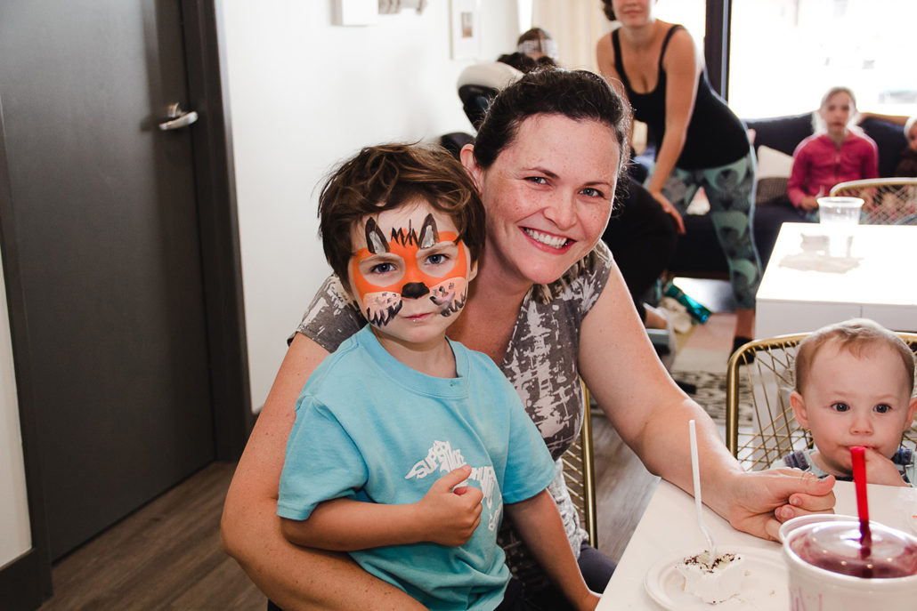 mom holding son with tiger face paint on his face