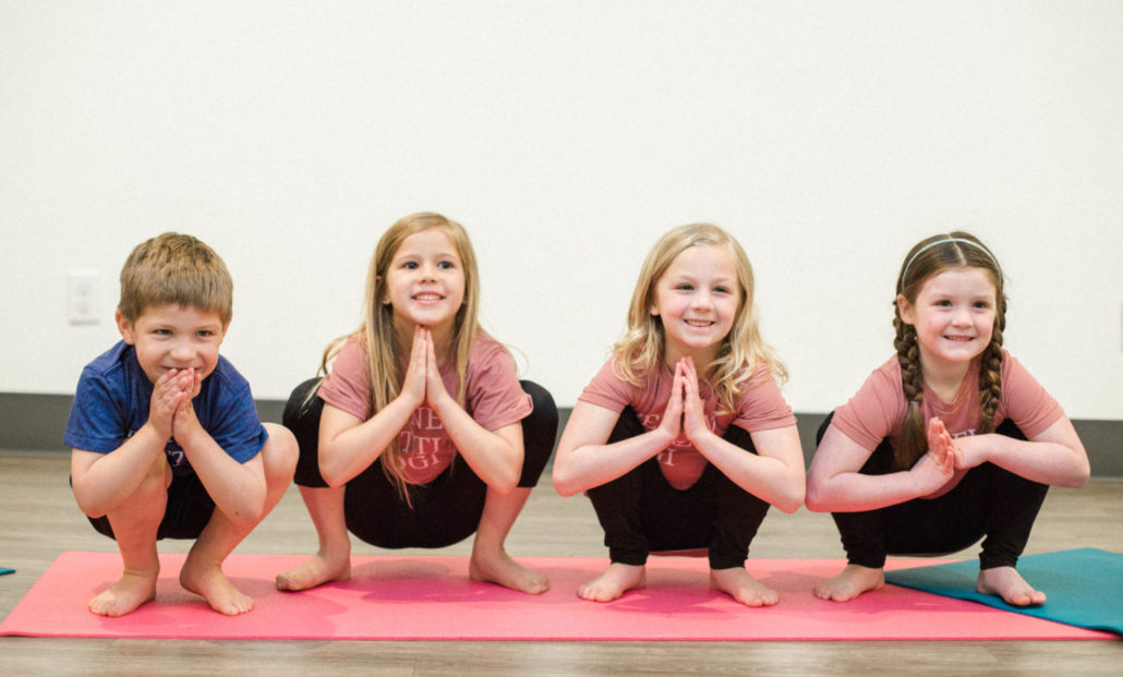 Four kids in Squat Pose, practicing yoga