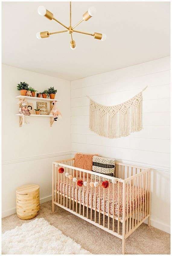 macrame wall hanging above crib in baby nursery