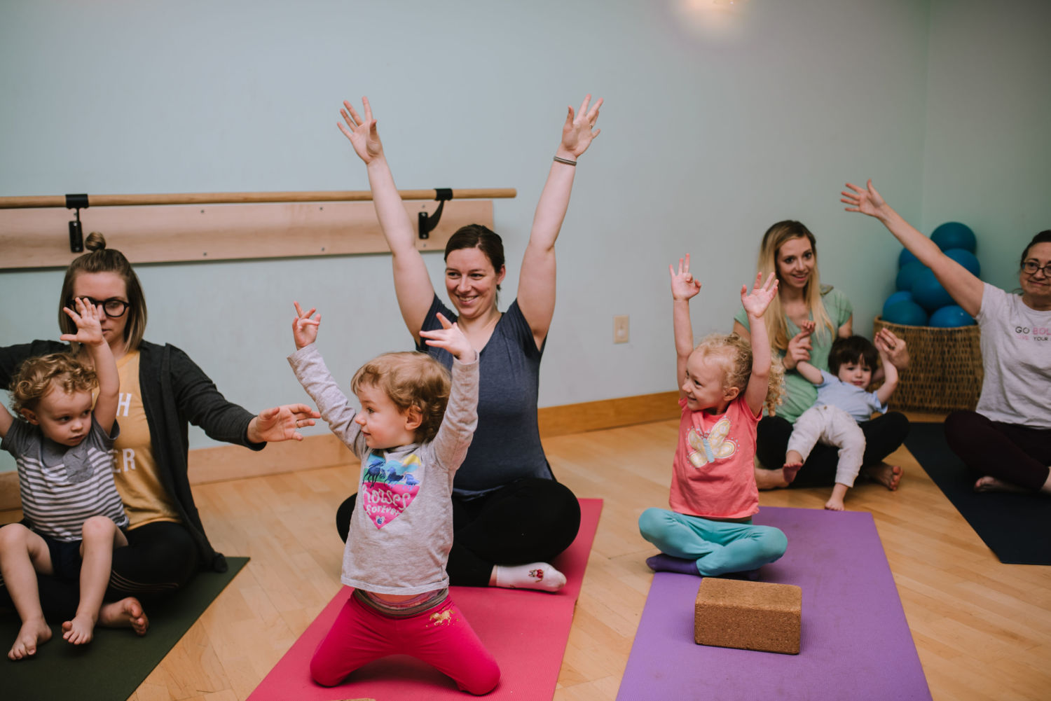 children and their parents practicing family yoga