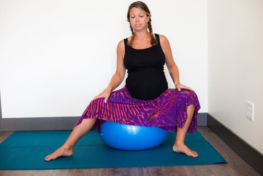 pregnant woman on yoga ball, moving from side to side