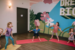 Five children playing in a kids yoga class