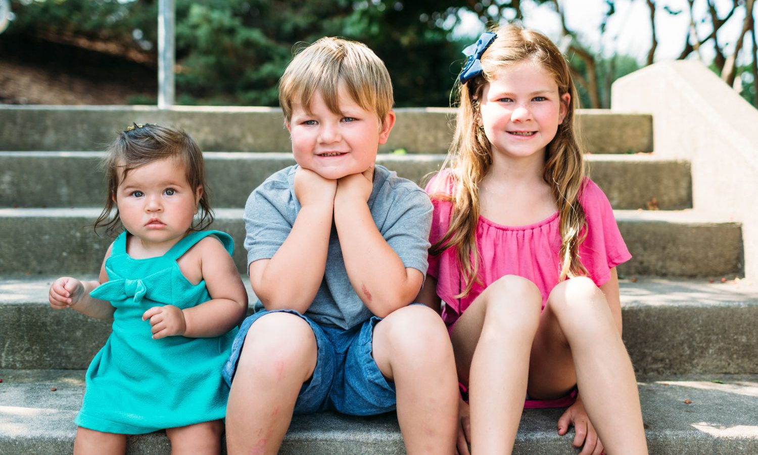 three kids sitting on outdoor steps