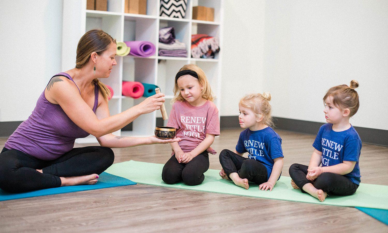 teacher handing singing bowl to kids in a yoga class