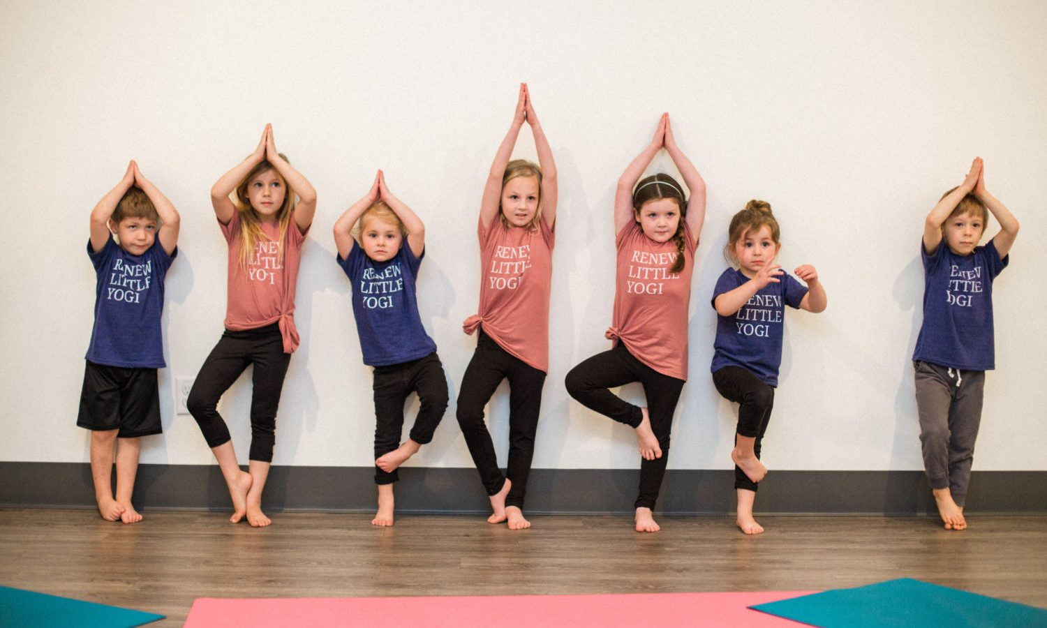 Seven kids in Tree Pose practicing yoga